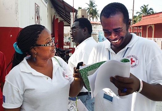 Two Haitian Red Cross volunteers talking and lokking at papers with data