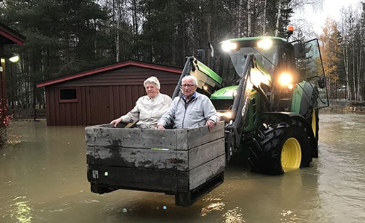 An old couple is seen rescued from the floods sitting and a wooden box lifted by a tractor